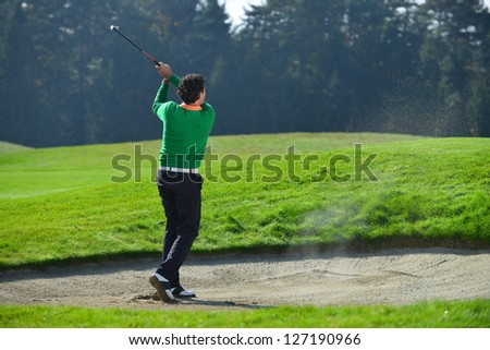 Golfer chipping the ball from sand trap, golf ball in the air. - stock photo