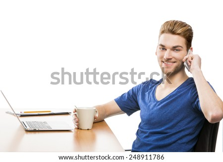 Good looking young man working in the office and talking at phone - stock photo
