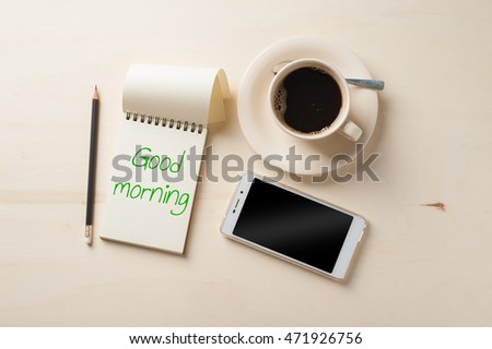 """Good morning"" is written on opened notebook with blank area, pen, smart phone, and coffee cup on wood table in morning time"
