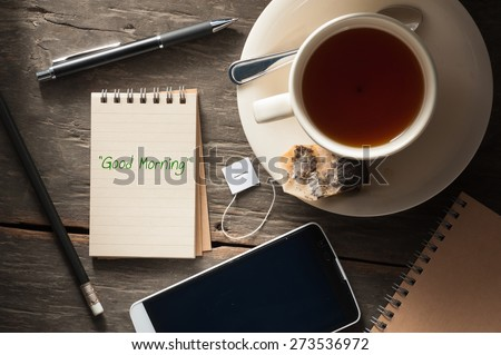 """""""Good morning"""" is written on small notepad with a cup of tea, pen, pencil and cellphone on rustic wood background with low key scene - stock photo"""