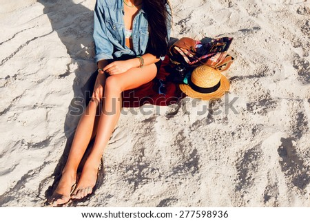 Gorgeous sexy woman with perfect tan body, full red lips and l  long legs posing on the  tropical  sunny beach. Wearing  crop top , shorts and straw hat. Bright sunny colors. - stock photo
