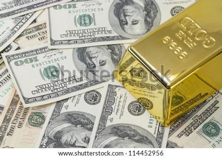 1000 grams or kilo golden bar on background of hundred dollar ba - stock photo