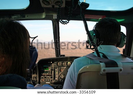 """Grand Canyon Flight"" Helicopter interior during flight, focus on pilot. - stock photo"