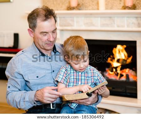 grandfather and grandchild reading a book - stock photo