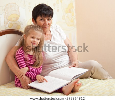 grandmother and granddaughter reading a book - stock photo