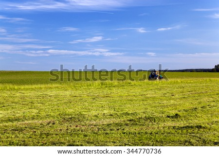 grass mowing tractor in agricultural field. - stock photo