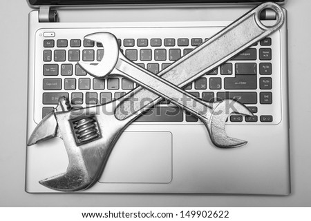 gray laptop with a vanadium spanner on the keyboard Two metal tools on the computer symbol repair, software installation, upgrade, improvement - stock photo