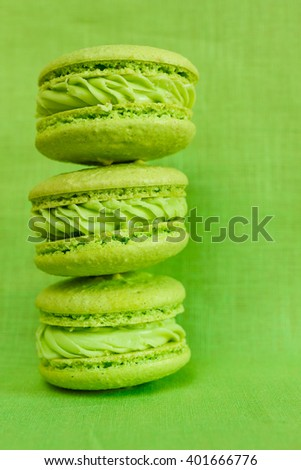 green and yellow macaroons. Three macaroon on a green background