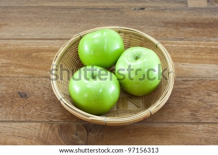 3 green apples on basket with teak wood background.