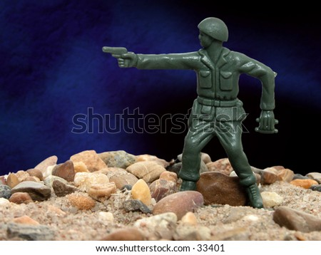 Green army man standing on rocks and sand in front of a studio background. - stock photo