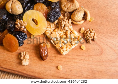 Grilyazh, candied roasted nuts and dried fruits, dried pineapple, dried figs, walnuts, prunes, figs, dried apricots on wooden board - stock photo