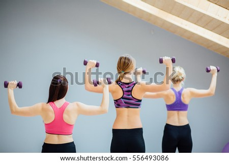 Group Of Three Women doing exercise with dumbbells in fitness studio.