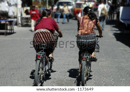 2 Guataemalan Indian women riding bicycles - stock photo