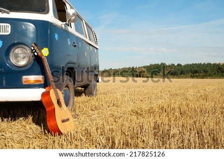 guitar in front of a detail camper van in a field