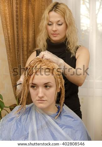 hairdresser paint customer's hair in the salon - stock photo