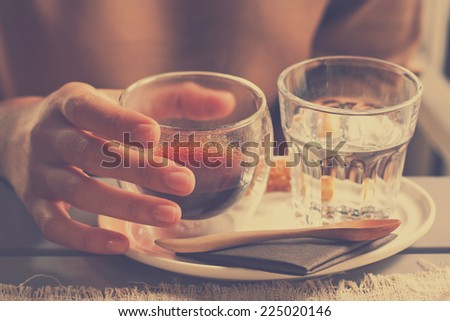 hand holding a freshly brewed cup of hot black coffee americano,drinking water in retro filter effect or instagram filter - stock photo