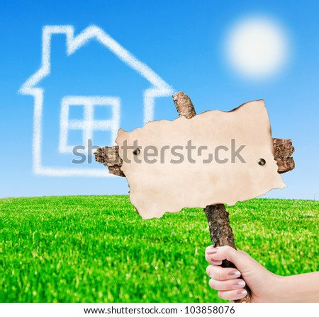 hand holding an empty plate on the background of the house from the clouds and blue sky - stock photo