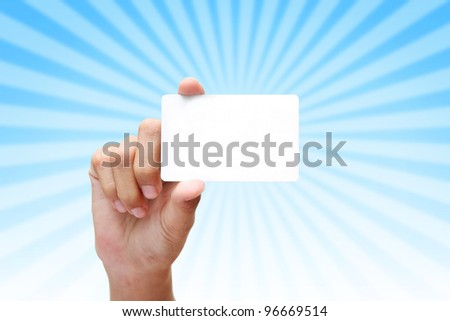 hand holding business card on rays of light blue background. - stock photo