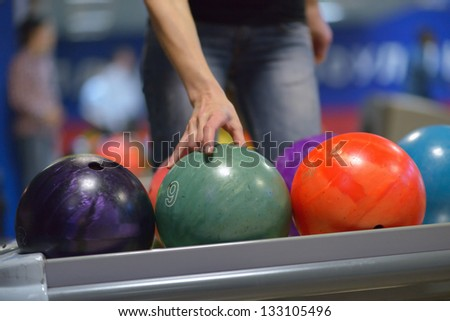Hand taking ball from bowling ball machine - stock photo
