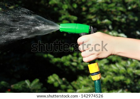 hand watering the plants on garden - stock photo