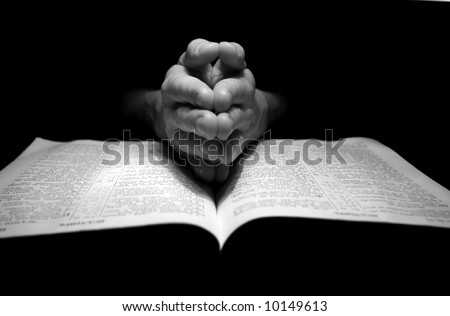 hands clasped in prayer over a  Bible - stock photo