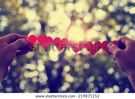 hands holding a string of paper hearts up to the sun during sun toned with a retro vintage instagram filter effect (shallow depth of field and sun flare) - stock photo
