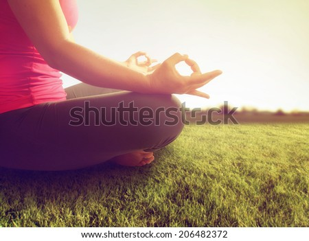hands of a woman meditating in a yoga pose on the grass toned with a soft sunny filter  - stock photo