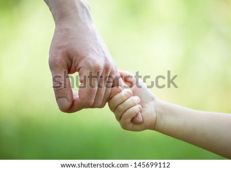 : Hands of man and child holding together on light green background - stock photo