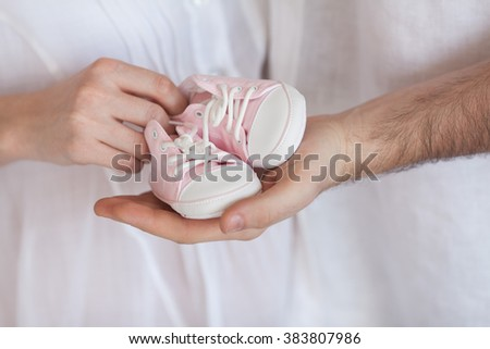 Hands of the woman holding small shoes for a baby. Waiting for the baby. The loving parents. Hands of the woman holding small shoes for a baby. - stock photo