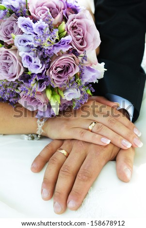 2 hands with wedding rings and flowers - stock photo