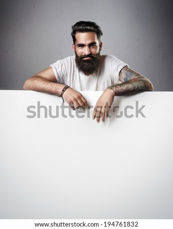 Handsome bearded man holding white poster. - stock photo