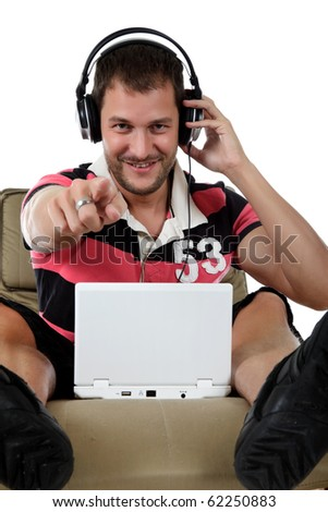 Handsome young caucasian man with headphones  and laptop on sofa and listening  music from the internet, pointing. Studio shot. White background. - stock photo