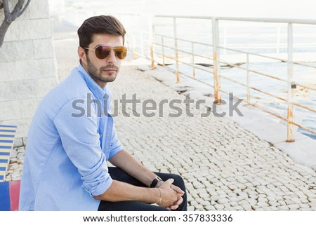 Handsome young man in bluejeans sitting on a bench nearby the sea - stock photo