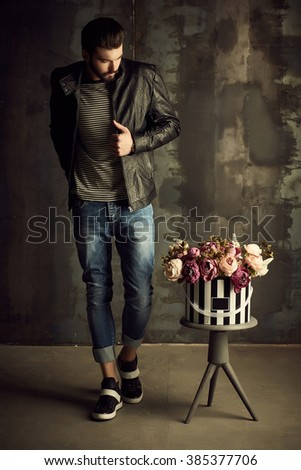 Handsome young man in smart jacket with bouquet of flowers  poses in front of the  wall