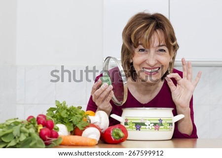 Happiness brown haired mature woman preparing  a meal and with hand showing sign OK while looking at camera. - stock photo