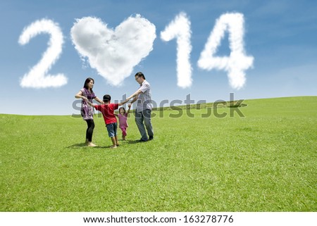 Happy asian family playing on the field. They are running in circle shot over blue sky  - stock photo
