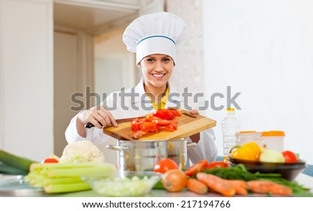 Happy beautiful cook woman in uniform prepares veggie lunch  at commercial kitchen