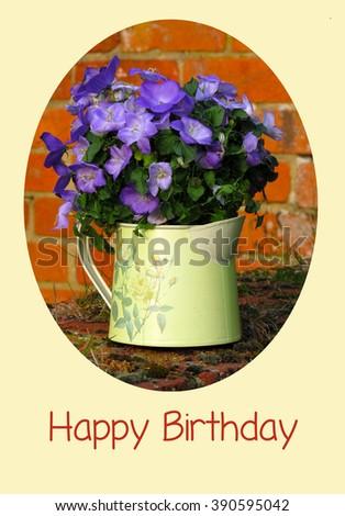 Happy Birthday card with purple Campanulas in a metal jug                      - stock photo