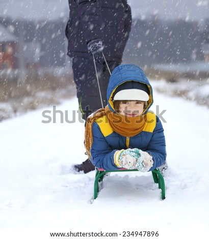happy boy on sled outdoors winter - stock photo