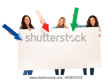 3 happy casual women presenting a big blank board by pointing arrows to it, isolated on white background - stock photo