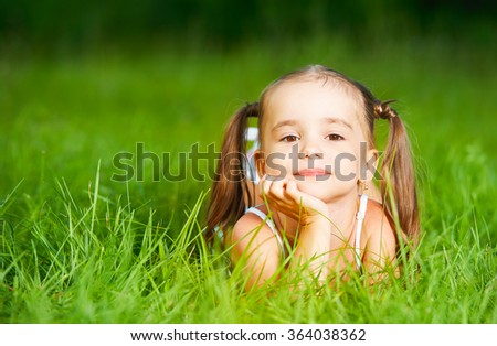 happy child little girl in a white dress lying on the grass Summer - stock photo