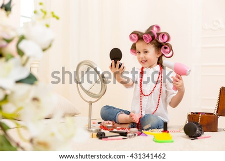 Happy child. Portrait of a pretty little girl looking in a small mirror and holding a pink hairdryer on a bed in the bedroom . Girl laughing with pink hair curlers on her head - stock photo