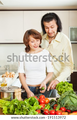 happy couple cooking vegetables in home kitchen