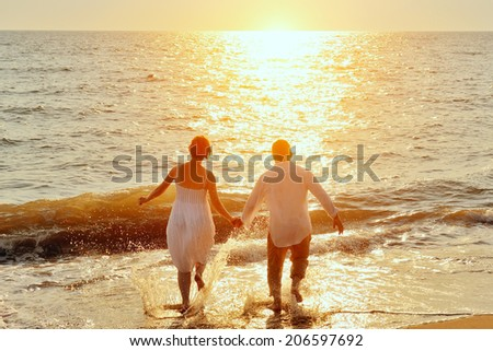 happy couple running to the sea on the beach at sunset