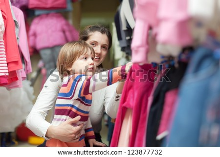 Happy family  chooses wear at fashionable shop. Focus on girl - stock photo