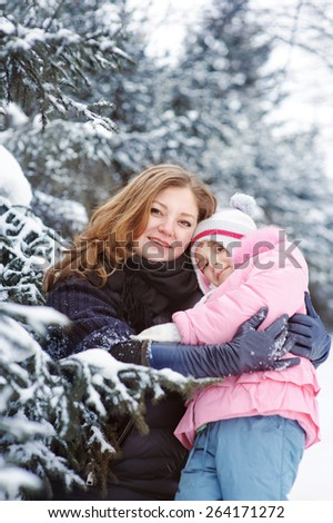 Happy family mother and baby girl daughter playing and laughing in winter snow - stock photo