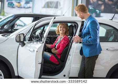 Happy female costumer at a showroom car setting in car