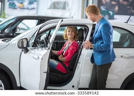 Happy female costumer at a showroom car setting in car  - stock photo