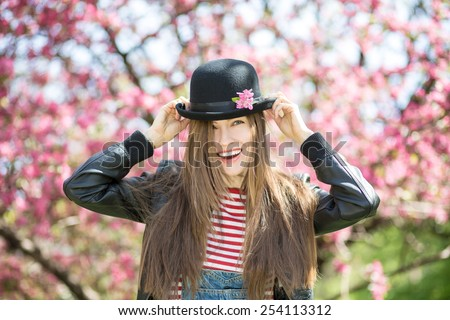 Happy hipster young woman in spring blossom park. soft backlight - stock photo
