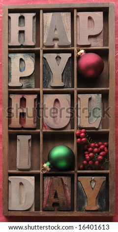 'happy holiday' in old wood letters in a type case with ornaments and berries - stock photo